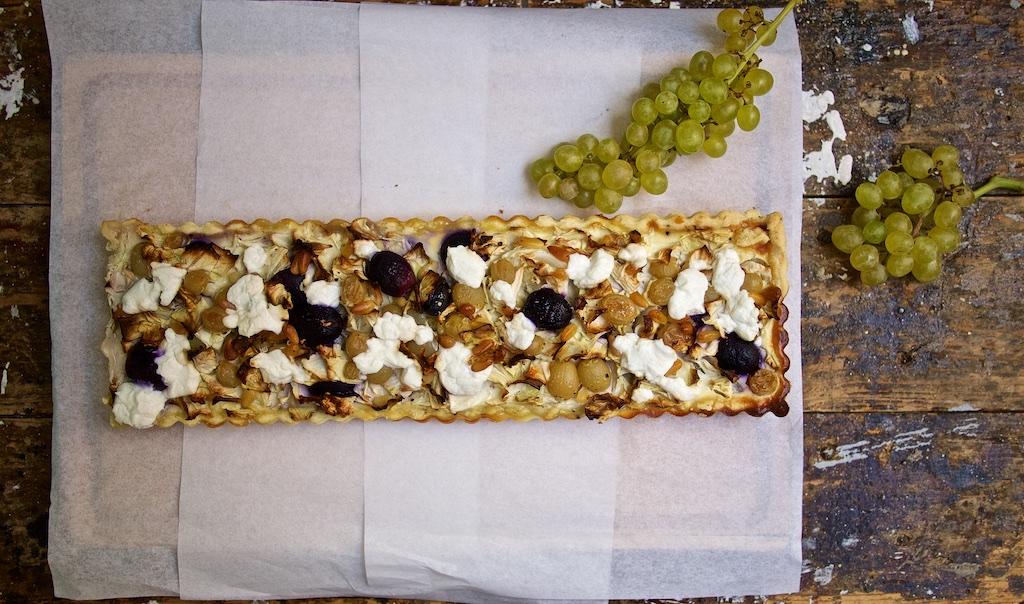 Spitzkohl-Ziegenkäse-Quiche mit Weintrauben und Pinienkernen